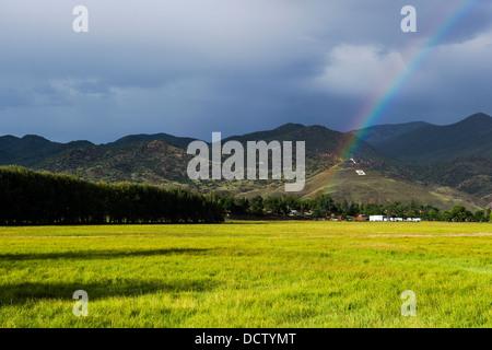 Rainbow over the small mountain town of Salida, Colorado, USA - Stock Photo