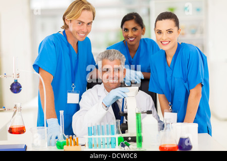 cheerful senior scientist with group of chemistry students in the lab - Stock Photo