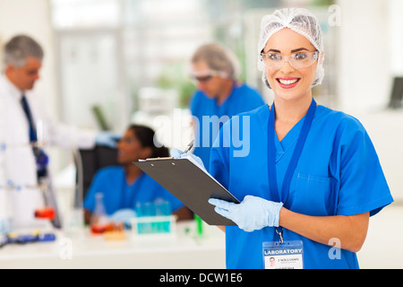 cheerful female medical researcher writing report after doing lab experiments - Stock Photo