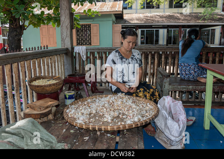 Woman peeling garlic for monk's midday meal - Stock Photo