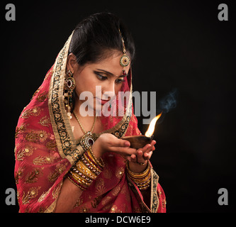 Beautiful young Indian woman in traditional sari dress holding a diwali oil lamp light, isolated on black background. - Stock Photo