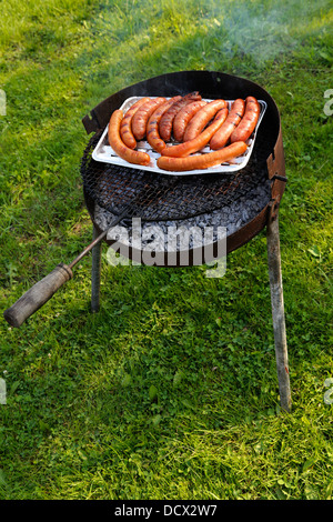 fresh sausages on a grill outdoor barbecue on the grass background - Stock Photo
