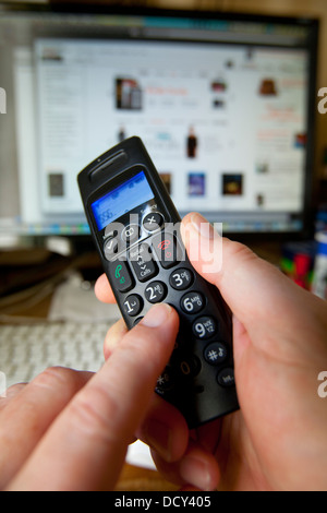 Hand Holding Dialing Phone Handset in front of Computer with Amazon on the screen - Stock Photo