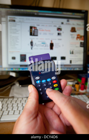 fingers keying Natwest Online Banking security card-reader in front of computer with Amazon on screen - Stock Photo