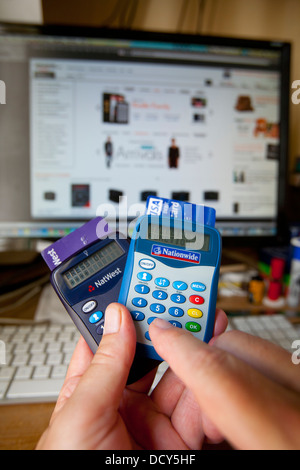 fingers keying Nationwide Building Society Online Banking security card-reader in front of computer with Amazon - Stock Photo