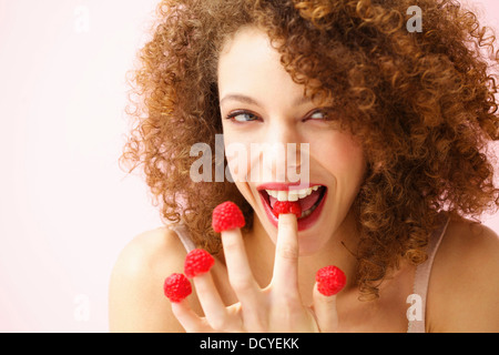 Smiling Young Woman Biting and Wearing Raspberries on Fingertips - Stock Photo
