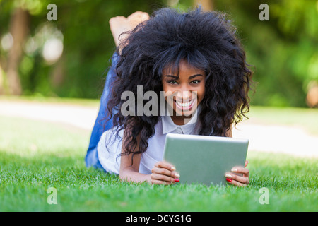 Outdoor portrait of a smiling teenage black girl using a tactile tablet - African people - Stock Photo