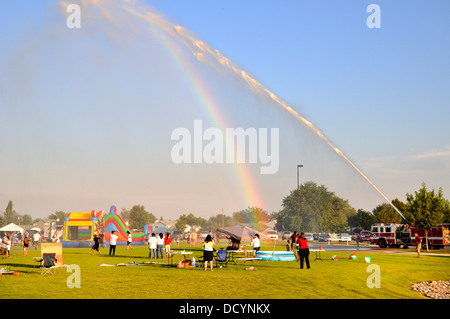 Fire truck spraying crowd at neighborhood gathering on a hot summer afternoon - Stock Photo