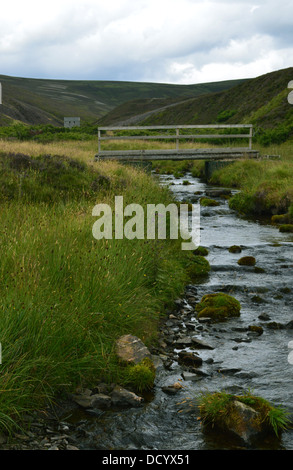 Wooden footbridge over burn near the disused iron mine at the Lecht at the foot of the Scottish Mountain Carn Mor - Stock Photo