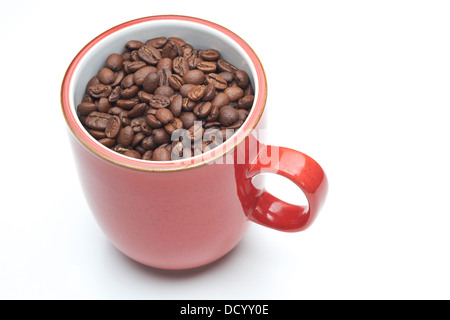 Red mug with coffee beans in it on a white isolated background. - Stock Photo