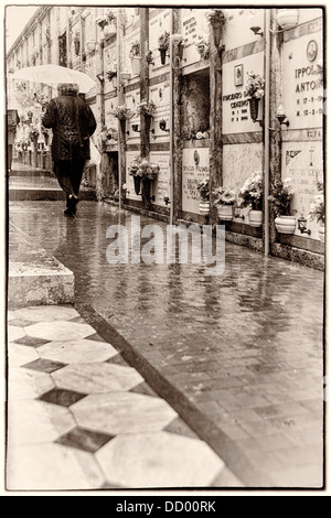 Single woman walking along diagonal path in rain, with umbrella, tombs in background reflected on wet path, Monterosso - Stock Photo
