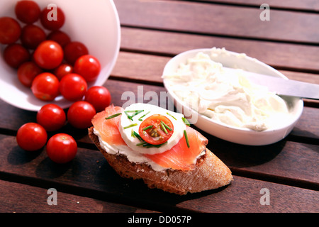 Close up of bread with salmon, tomatoes and cheese - Stock Photo