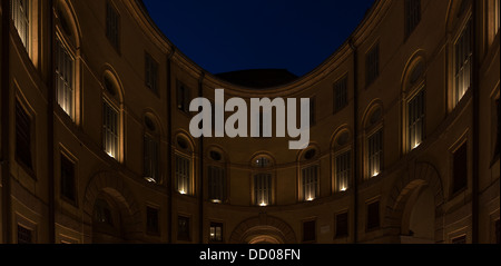 View looking up, Ferrara Theatre inner courtyard, with night sky above, illuminated circular building - Stock Photo