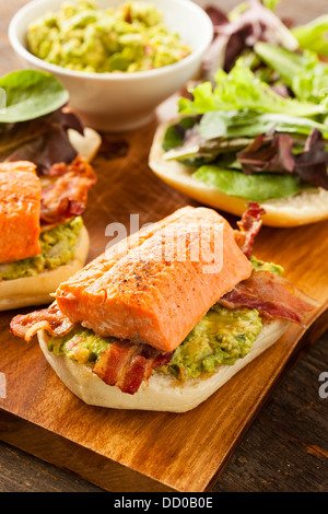 Grilled Salmon Sandwich with Bacon and Guacamole on Bread - Stock Photo