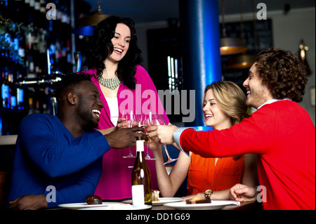 Two young couples in club or bar having fun, toasting wine glasses. - Stock Photo