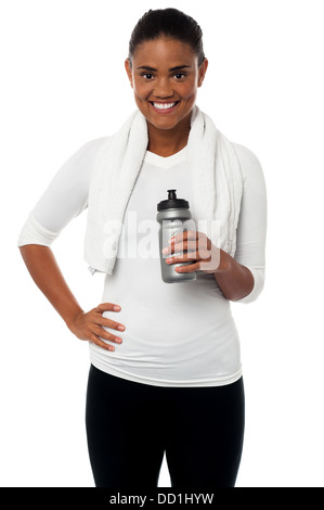 Fit smiling woman with towel around her neck, holding sipper bottle. - Stock Photo