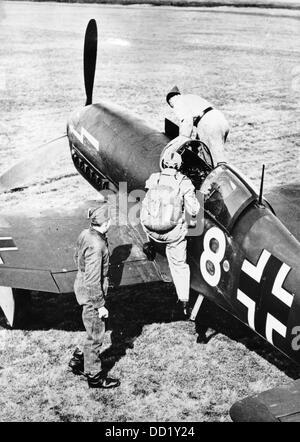 A pilot of the German Luftwaffe climbs into a combat aircraft of the type Heinkel He 113 in July 1942. Place unknown. - Stock Photo