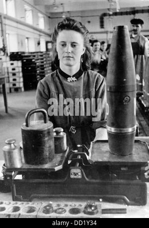 The image from the Nazi Propaganda! shows a young woman weighing grenades in an ammunitions factory in March 1941. - Stock Photo