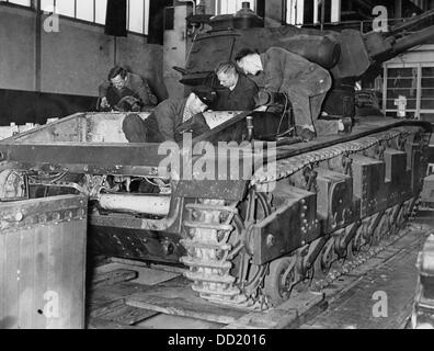 Four workers during the assemblage of a tank in a production hall. Date and place unknown. The Nazi Propaganda! - Stock Photo