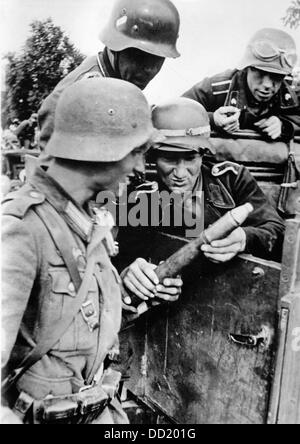 The image from the Nazi Propaganda! shows German members of an antitank unit examining grenades from a captured - Stock Photo