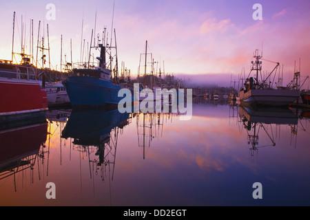 Sunrise Through The Morning Fog And Fishing Boats In Newport Harbor; Newport, Oregon, United States of America - Stock Photo