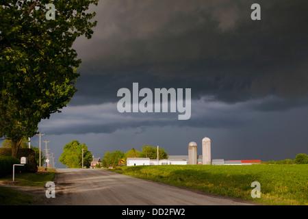 Storm Clouds Over A Farm; Farnham,Quebec, Canada - Stock Photo