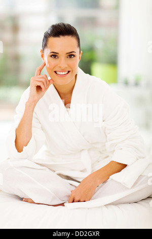 attractive woman wearing white bathrobe sitting on bed - Stock Photo