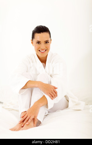 cheerful woman wearing nightgown sitting on bed - Stock Photo