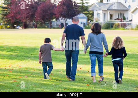 Family Walking Together In A Park; Beaumont, Alberta, Canada - Stock Photo