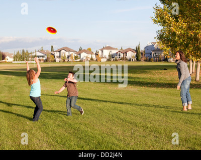 Mother Throwing Flying Disc To Children In A Park; Beaumont, Alberta, Canada - Stock Photo