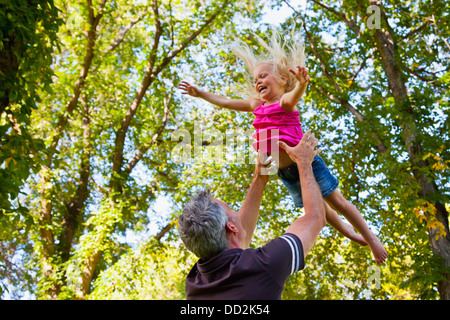 Father Throwing Toddler Daughter In The Air In A Park; Edmonton, Alberta, Canada - Stock Photo