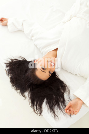smiling dark haired woman lying in bed - Stock Photo