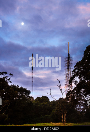 Mobile or cell phone masts in the Australian bush, under a full moon and a pink and purple twilight sky. Technology - Stock Photo