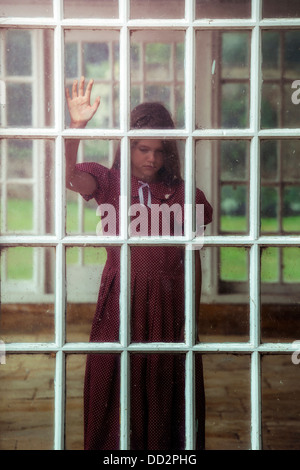 a girl is standing behind an old window - Stock Photo