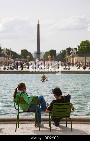 A couple sit in Jardin des Tuileries in front of Luxor Obelisk, Paris, France - Stock Photo