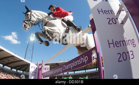 Herning, Denmark. 24th Aug, 2013. German show jumper Daniel Deusser jumps over a hurdle on his horse Cornet D'Amour - Stock Photo
