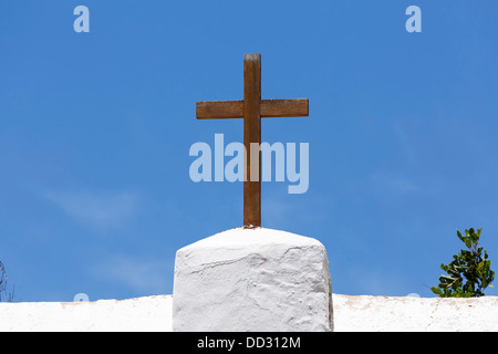 Wooden cross on a white church against a blue sky in Spain - Stock Photo