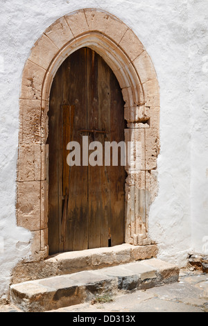 Historic arched wooden door to an old Spanish church - Stock Photo