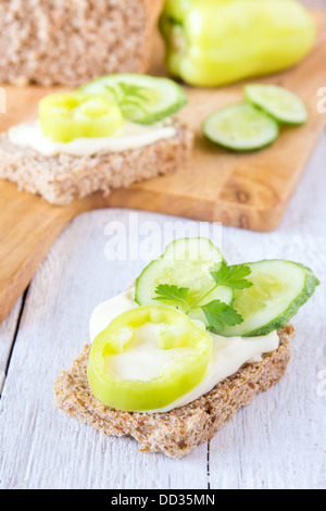 Vegetarian sandwich (snack) with wholegrain bread, cheese and vegetables (pepper, cucumber, parsley) close up vertical - Stock Photo