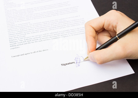 Hand signing a contract - Stock Photo