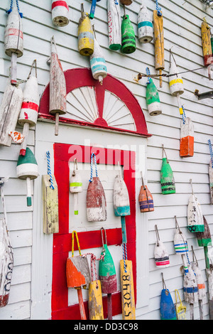 Differing colors of wooden buoys used in fishing for lobster and crab hang from the side of a house in Maine. - Stock Photo