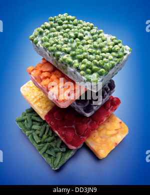 A large stack of frozen blocks of food; green peas, carrots, blackberries, corn, strawberries, peaches and green - Stock Photo