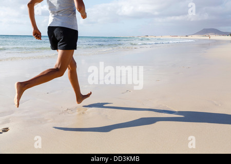 Fit Asian runner jogging on beach barefoot - Stock Photo