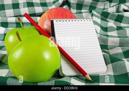 note book with red pencil and apples - Stock Photo
