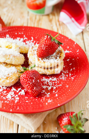 cottage cheese pancakes with strawberries and coconut, close up - Stock Photo