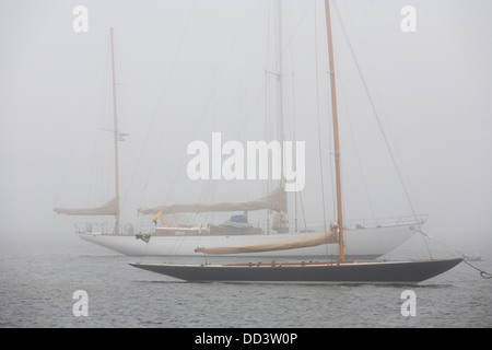 Classic yachts and sailing boats lie at their moorings in Newport RI on a foggy day. They have sail covers with - Stock Photo