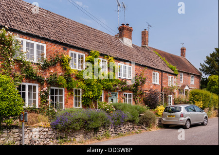 A row of terraced red brick cottages in Steeple Langford , Wiltshire , England , Britain , Uk - Stock Photo