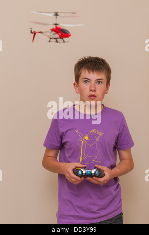 A 13 year old boy flying his radio controlled helicopter indoors - Stock Photo