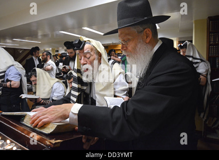 With help from his son-in-law an 88 year old man orthodox Jewish man leads morning prayer services at Lubavitch - Stock Photo
