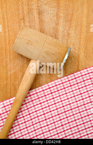 Meat tenderizer on wooden kitchen table, checkered table napkin in background. - Stock Photo